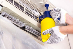Technician spraying chemical water onto air conditioner grid to clean