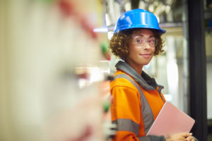 A female industrial service engineer has just conducted a safety check of a control panel in a boiler room. She is wearing hi vis, hard hat, safety glasses and holding a digital tablet that she used to conduct a safety inspection. The engineer is stated next to the control panel looking to camera and smiling.