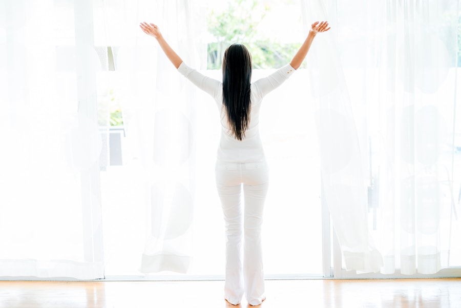 Woman opening the windows at home and enjoying some fresh air.